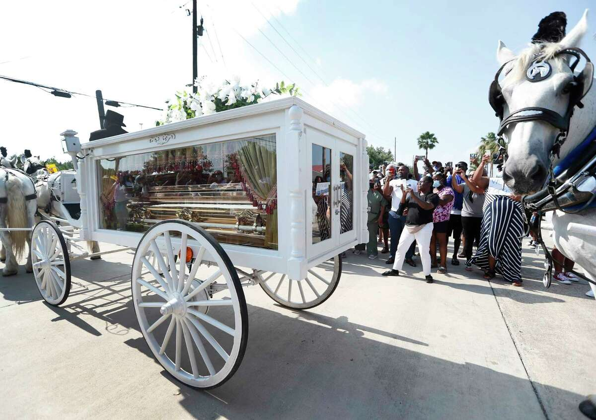 George Floyd's casket carried by a horse drawn carriage inches past the crowd of people along Cullen Blvd. Tuesday, June 8, 2020.