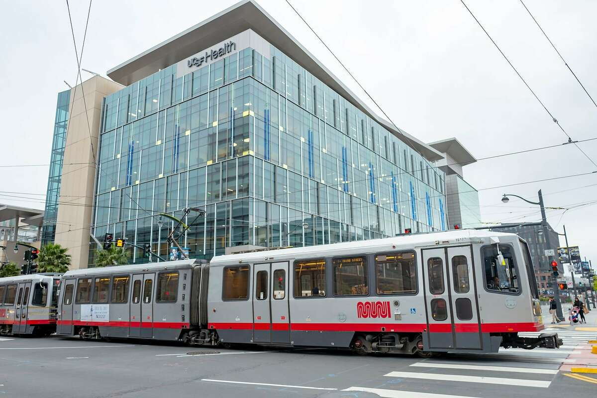 FILE - A San Francisco Municipal Railway (MUNI) train passes by the UCSF Mission Bay medical center in San Francisco on March 23, 2020.
