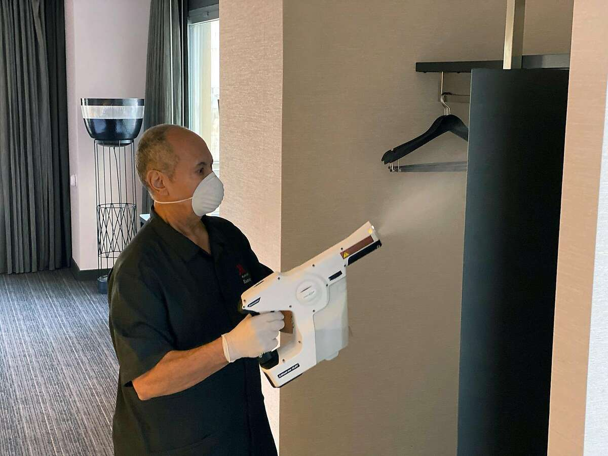 An undated photo provided by Marriott shows an employee using electrostatic spraying technology to kill germs in a hotel room. Hotel companies are coming out with new cleaning standards inspired by those set by the CDC. (Marriott via The New York Times) -- FOR USE ONLY WITH NYT STORY SLUGGED LODGING OUTLOOK BY ELAINE GLUSAC FOR MAY 17, 2020 -- ALL OTHER USE PROHIBITED. --