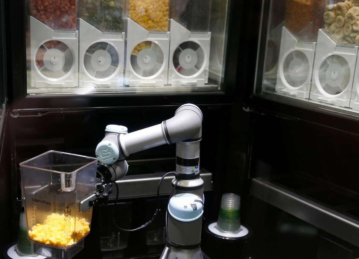An automated smoothie-making kiosk developed by Blendid handles a pitcher of mangos in a test run at the Market Cafe on the USF campus in San Francisco, Calif. on Friday, March 22, 2019. The robotic smoothie kiosk goes fully operational on Monday.