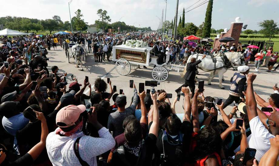 People gather around as the horse drawn carriage carrying the body of George Floyd makes the turn from Cullen Blvd. to Houston Memorial Gardens on Tuesday, June 9, 2020, in Pearland. Photo: Jason Fochtman, Houston Chronicle / Staff Photographer / 2020 © Houston Chronicle