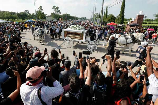 People gather around as the horse drawn carriage carrying the body of George Floyd makes the turn from Cullen Blvd. to Houston Memorial Gardens on Tuesday, June 9, 2020, in Pearland.