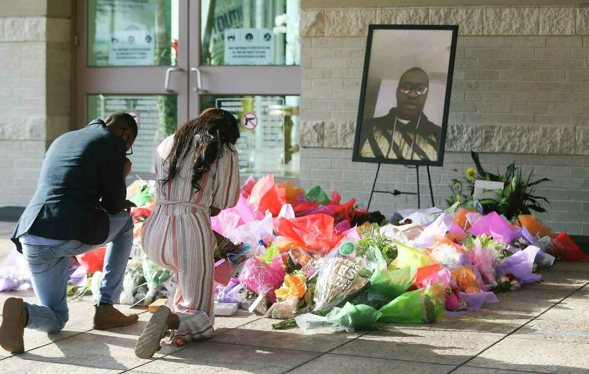 Mourners pause in front of memorial outside The Fountain of Praise Church before the funeral for George Floyd in Houston on Tuesday, June 9, 2020.
