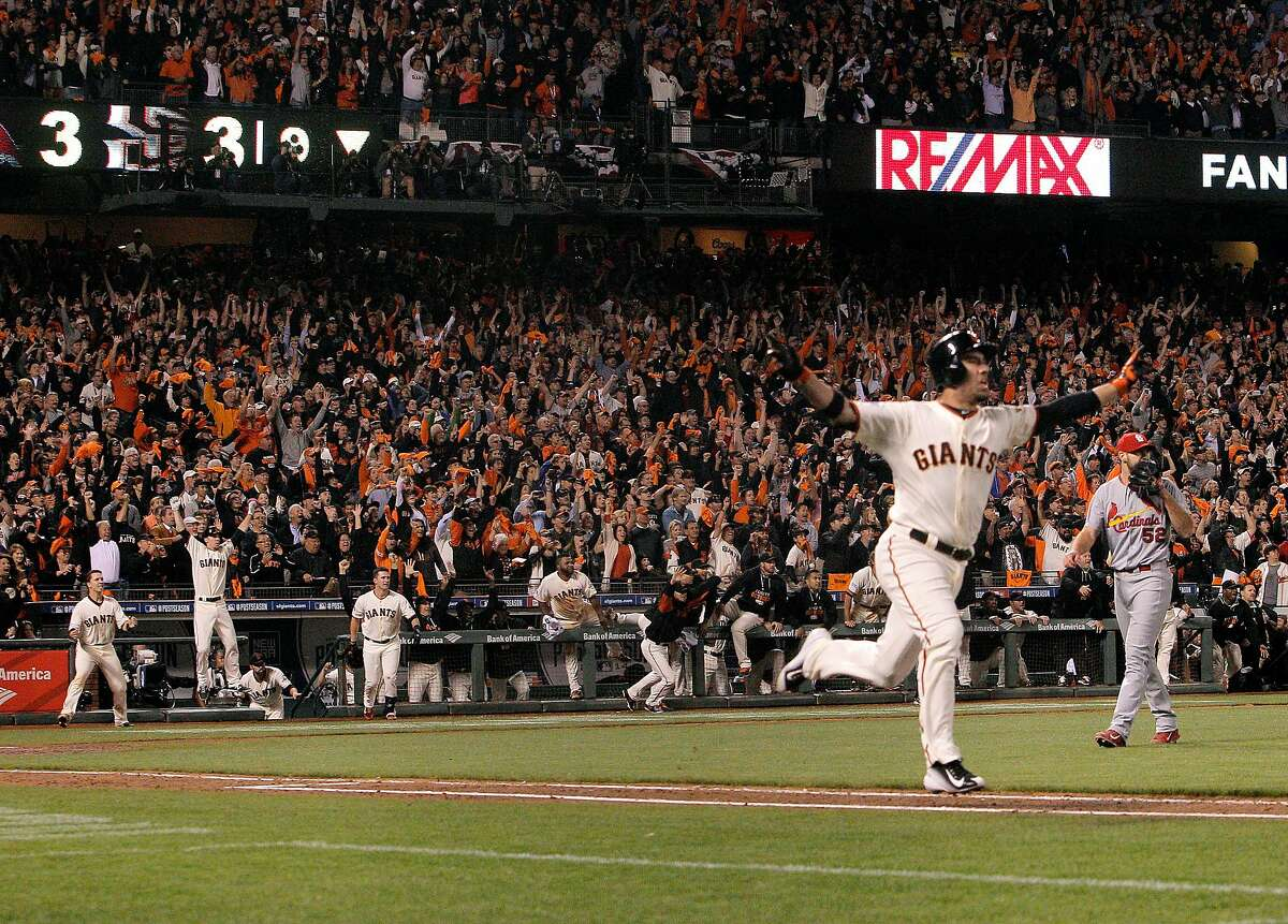 The Giants Travis Ishikawa raises his arms in celebration as he heads to first base on his three-run walk off home run while Cardinals losing pitcher Michael Wacha, right watches the hit during Game 5 of the NLCS at AT&T Park on Thursday, Oct. 16, 2014 in San Francisco, Calif.