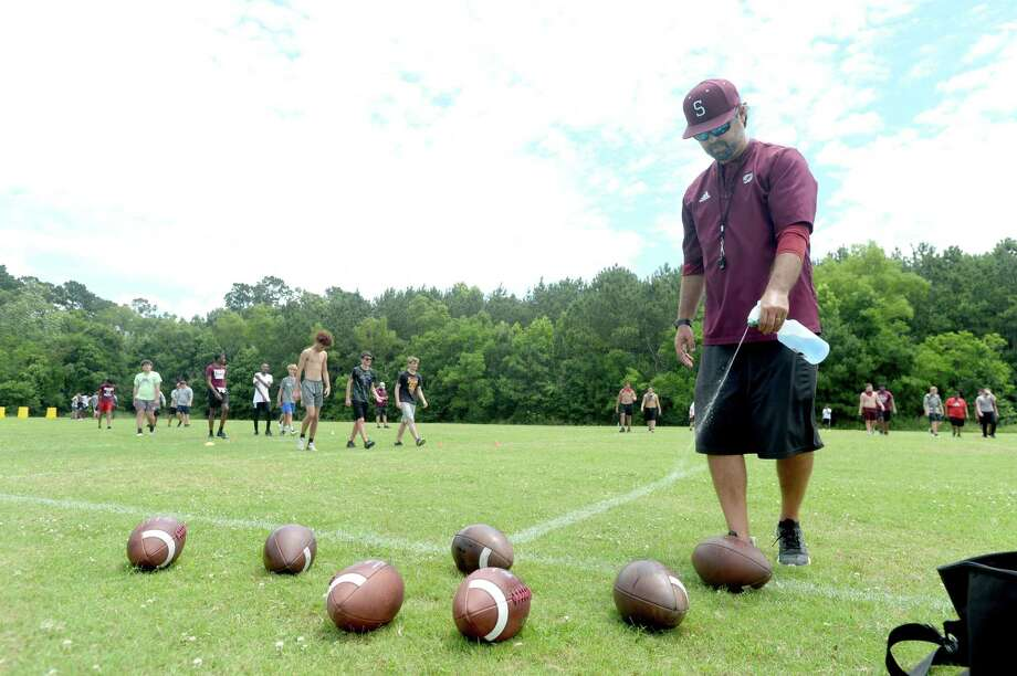 Coach Michael Nelson sprays disinfectant on footballs at the end of Silsbee High School's football first coniditioning practice of the 2020 season Monday morning. It was the first day that team practices were allowed in the state under guidelines issued to schools by TAPPS and UIL.  Photo taken Monday, June 8, 2020 Kim Brent/The Enterprise Photo: Kim Brent / The Enterprise / BEN