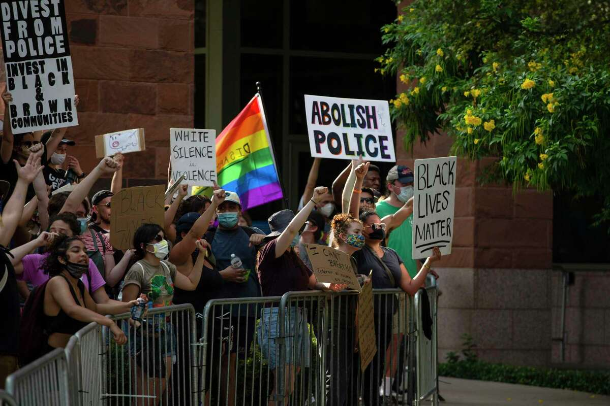 Protesters face law enforcement officers with their signs outside the Paul Elizondo Tower Building in downtown San Antonio, Texas, on June 9, 2020. Protesters rallied a day after Bexar County District Attorney Joe Gonzales said he did not plan to reopen the cases of Marquise Jones, Charles Roundtree and Antronie Scott, all of whom were killed by San Antonio police officers.
