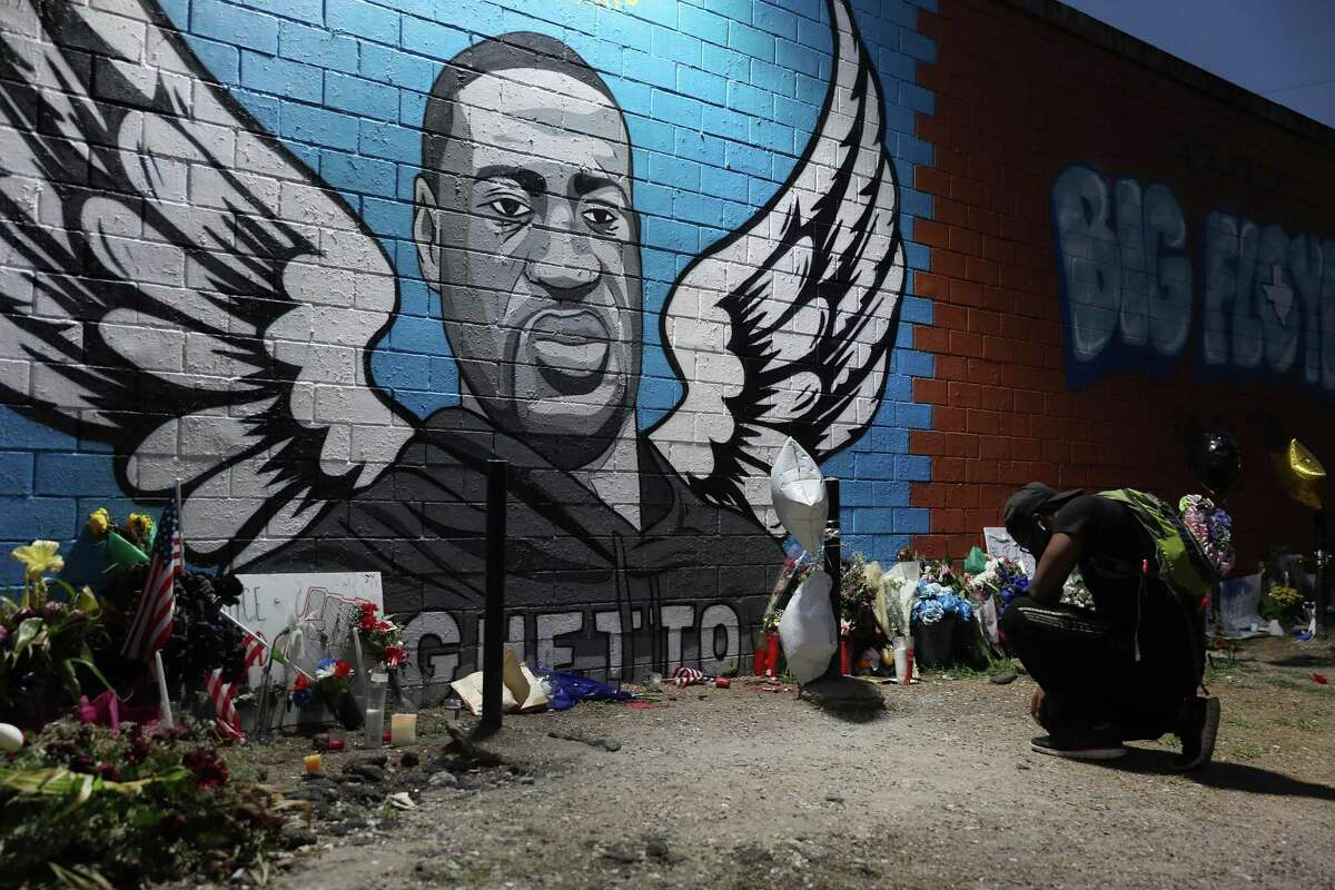 HOUSTON, TEXAS - JUNE 08: Joshua Broussard kneels in front of a memorial and mural that honors George Floyd at the Scott Food Mart corner store in Houston's Third Ward where Mr. Floyd grew up on June 8, 2020 in Houston, Texas. The funeral and burial for George Floyd will be held June 9. Floyd died on May 25th while in Minneapolis police custody, sparking nationwide protests. (Photo by Joe Raedle/Getty Images) ***BESTPIX***