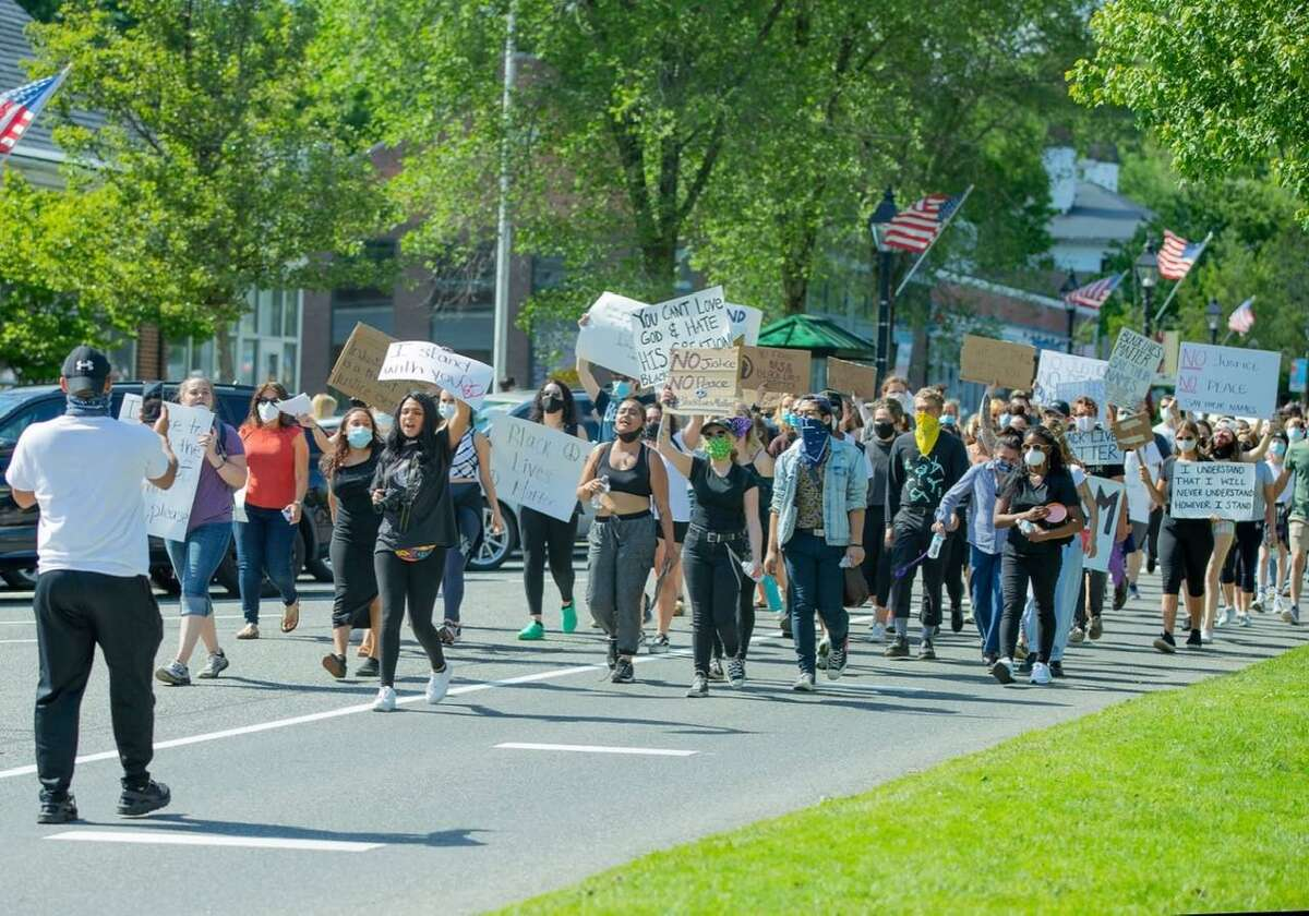 A crowd of protesters march down the west side of Main Street in New Milford Sunday during a Black Lives Matter protest,