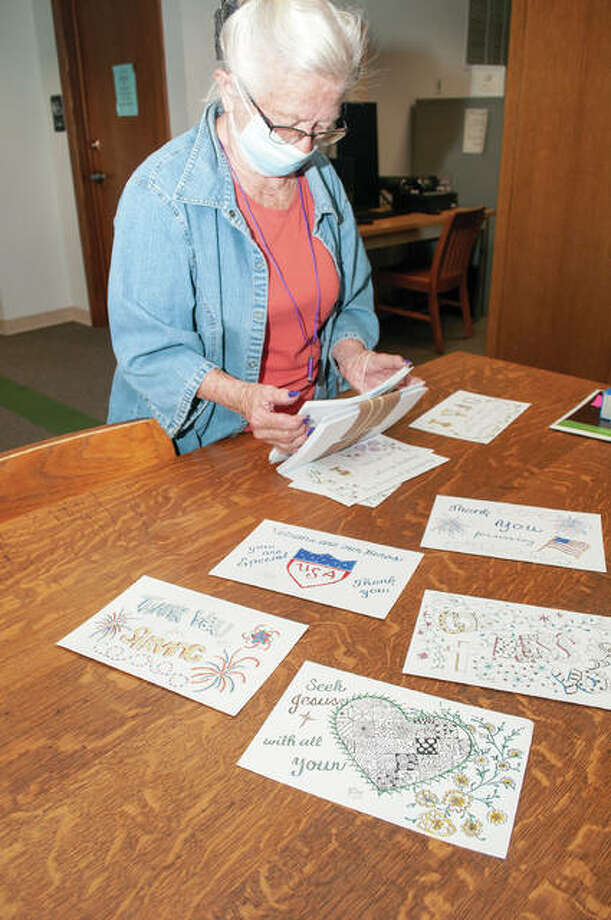 Lin Beeley, owner and operator of For Your Love Petting Zoo, pulls out her hand-drawn cards that she will be sending to the Illinois Veterans Home in Quincy. Photo: Darren Iozia | Journal-Courier