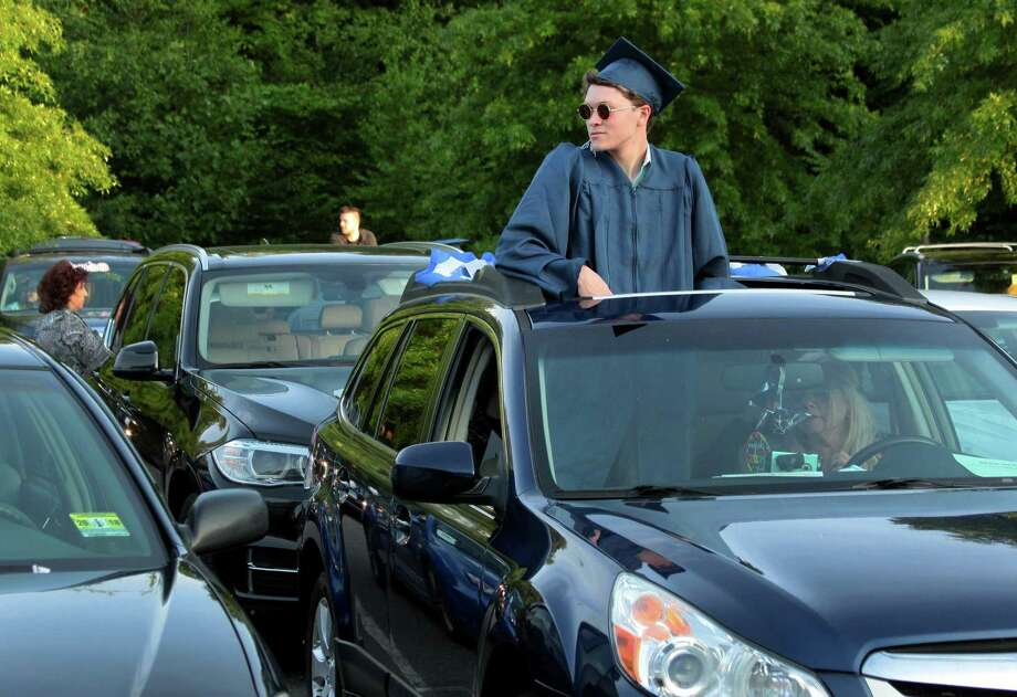 Graduate Sean Michael Garrison watches from outside the family vehicle's sunroof during Oxford High School's Class of 2020 Commencement in Oxford, Conn., on Tuesday June 9, 2020. Oxford is one of the first graduations in Connecticut to be held in the midst of the COVID-19 pandemic. Photo: Christian Abraham / Hearst Connecticut Media / Connecticut Post