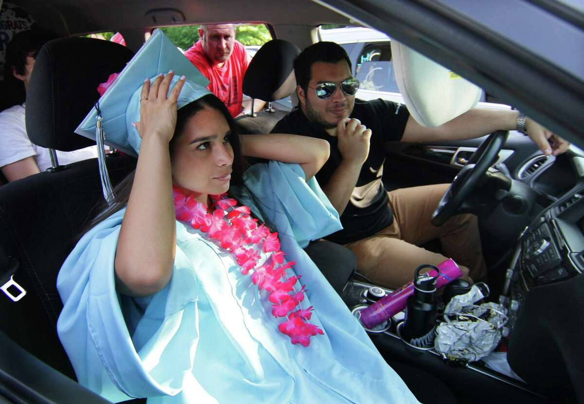 Graduate Melissa Cabezas adjust her graduation cap inside the family vehicle during Oxford High School's Class of 2020 Commencement in Oxford, Conn., on Tuesday June 9, 2020. This was the first graduating class for Superintendent of Schools Jason McKinnon. He told the graduates about growing up in Australia in a single parent home, having problems reading; his only goal was to work in a mine. Now, the superintendent said, he is attempting to address diversity issues in town.