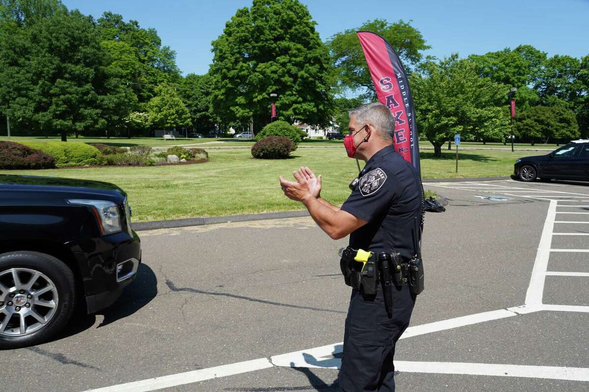 School Resource Officer Jeffrey Deak helps say farewell and congratulations to eighth graders as they celebrate their graduation at Saxe Middle School in New Canaan June 9.