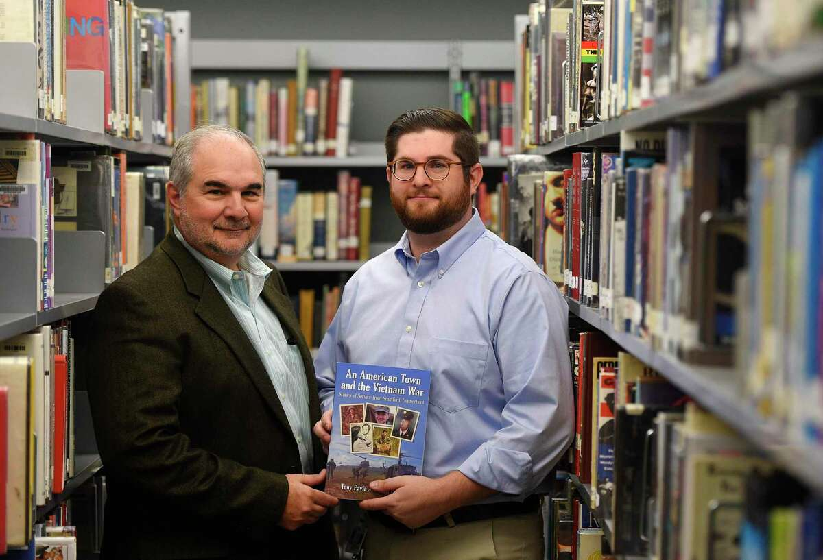 """Stamford resident Tony Pavia and his son, Matt Pavia, a teacher at Darien High School, show their new book """"An American Town and the Vietnam War"""" during a reception at Darien High School in Darien, Conn. Monday, Nov. 11, 2018. The book documents stories of Stamford veterans and their service in the Vietnam War."""