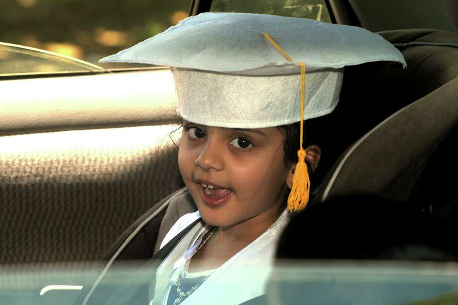 Aaliah Bangi smiles from the back seat of her family's car as she arrives to pick up her diploma at Skane School, in Bridgeport, Conn. June 8, 2020. The school held a drive-through graduation event for Pre-k students on Monday. Photo: Ned Gerard / Hearst Connecticut Media / Connecticut Post