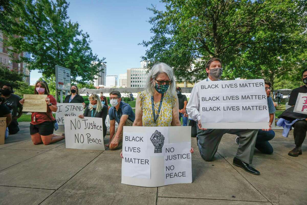 Jani Maselli (center) takes a knee to acknowledge the amount of time that Derek Chauvin kneeled into the neck of George Floyd as they joined other Public Defenders, family and friends in support of black lives matter across from the Harris County Criminal Justice Center Monday, June 8, 2020, in Houston.