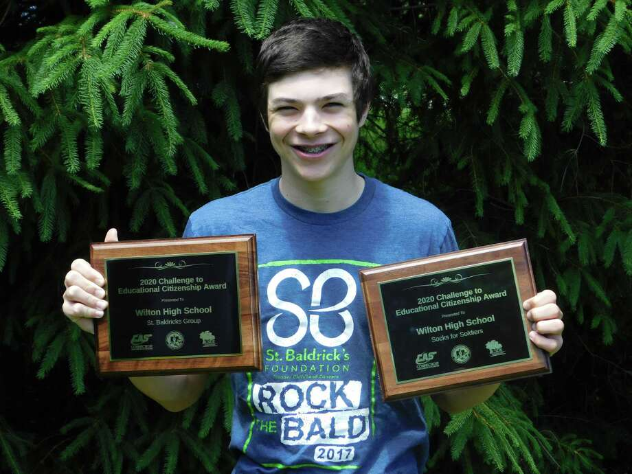 Wilton High School student Elijah Ackerman holds Connecticut Association of Schools awards for the Socks for Soldiers and St. Baldrick's programs that were given out virtually on June 9. Photo: Daniel Pompa / Contributed Photo / Wilton Bulletin Contributed