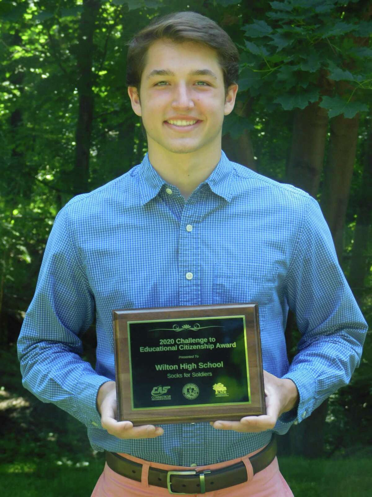 Wilton High School senior Jake Zeyher holds a Connecticut Association of Schools award for the Socks for Soldiers program that was given out virtually on June 9.