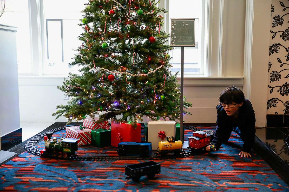 On Christmas Eve, homeless child Theo Schrager, 7, plays with toys under the Christmas tree at the Shattuck Plaza Hotel where he has been living with his mother on Tuesday, December 24, 2019 in Berkeley, California. Theo has been homeless since he was born. For nearly two years, Theo and his mother have been sleeping on the streets and in hotels after their RV was towed in July of 2018. Theo says he wants a home where he can ?'bake chocolate cakes in an oven?