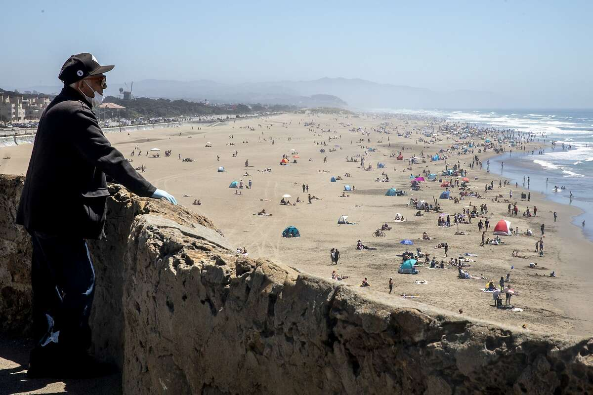 A older man wearing a mask and gloves looks out on crowds gathered at Ocean Beach in San Francisco, Calif. Monday, May 25, 2020. The warm Memorial Day weather brought out large crowds to popular parks and beaches despite the shelter-in-place order amid the COVID-19 pandemic.