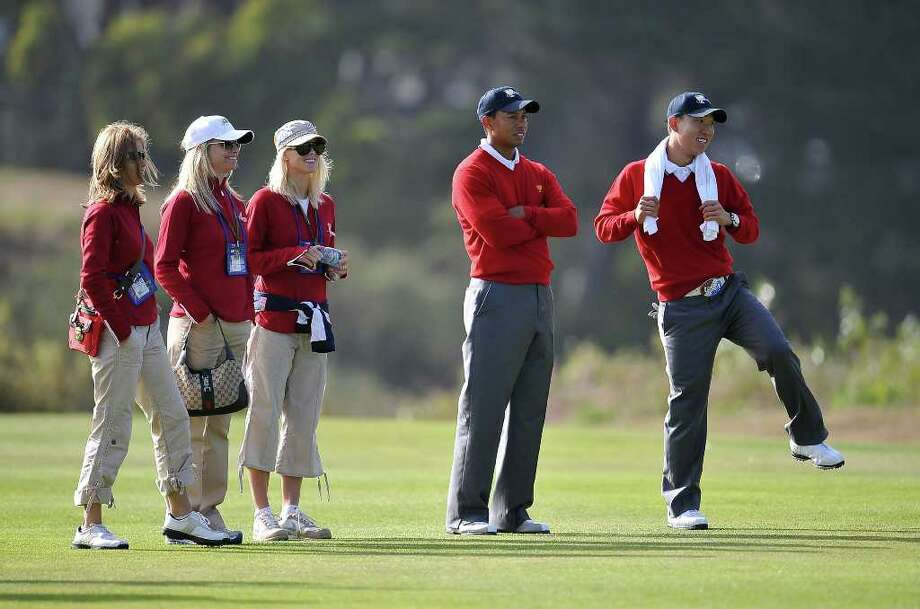 US Team members Tiger Woods and Anthony Kim watch their teammates play on the 15th hole with Woods' wife Elin Nordegren and two other unidentified guests of US Team members, on the first day of the Presidents Cup golf competition on October 8, 2009, at Harding Park Golf course in San Francisco, California. (Robyn Beck / Getty Images) Photo: ROBYN BECK / AFP