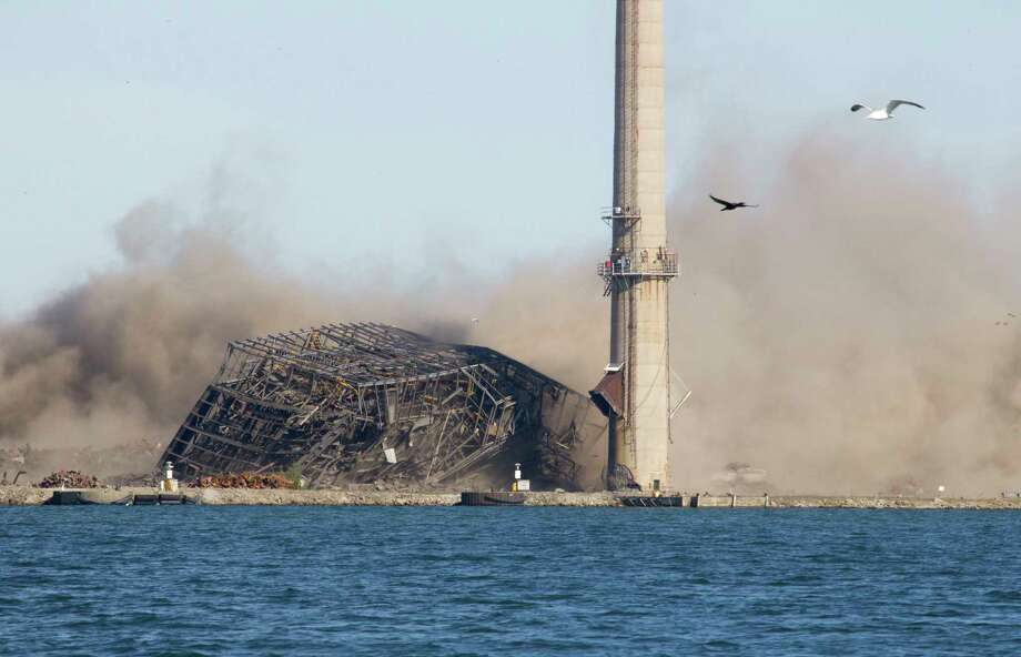 The smokestack remains standing Tuesday as the rest of the building is demolished at the former DTE Energy coal plant in Harbor Beach. Contractors said the stack not falling on the first explosion was by design. (Aurora Abraham/Huron Daily Tribune)