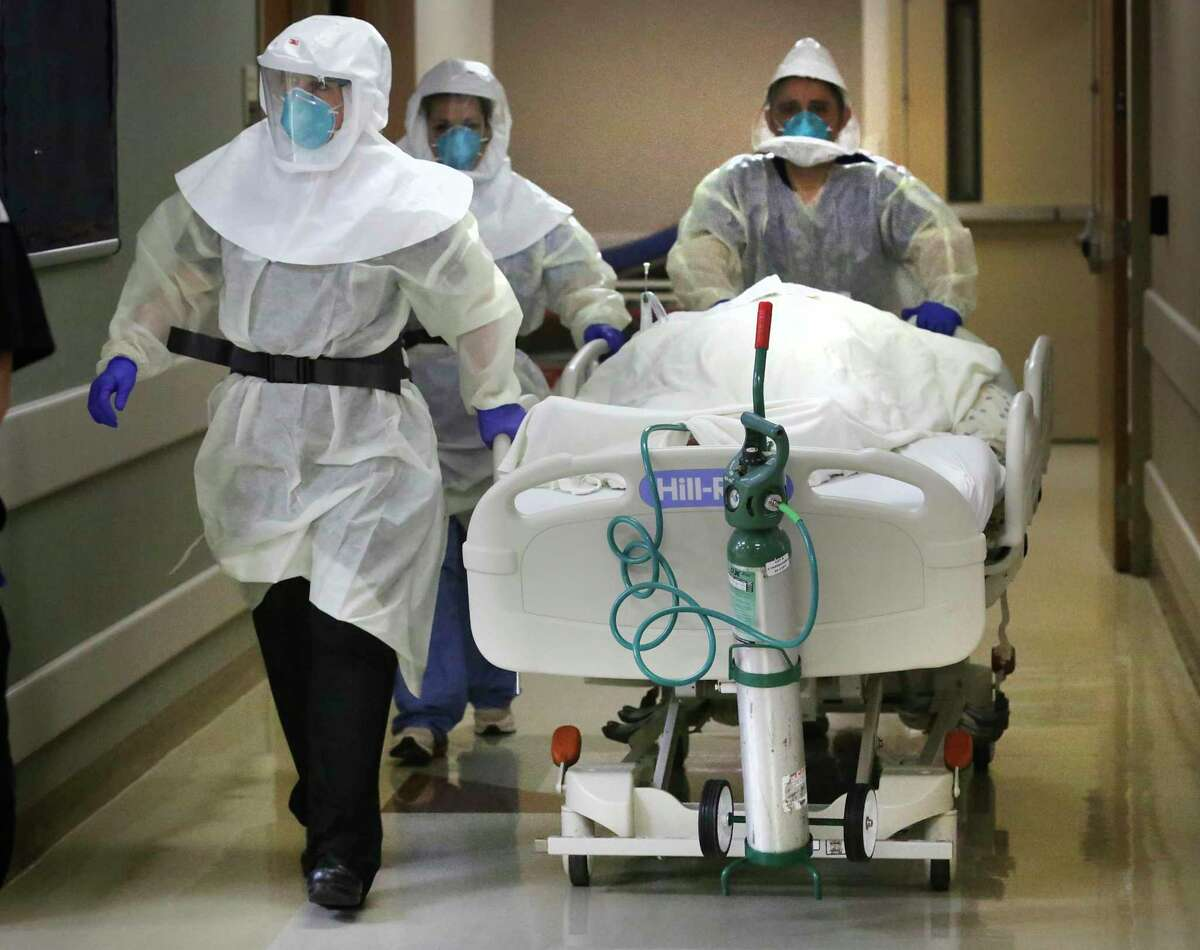 Dr. Tamara Simpson, left, and two nurses rush a covid patient to the Covid Unit at the Northeast Baptist Hospital Covid Unit, on Friday, April 24, 2020.