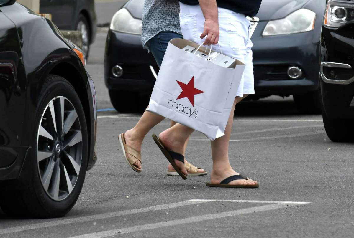 Shoppers head back to their car with a bag of goods from Macy's department store on Wednesday, June 10, 2020, at Colonie Center in Colonie, N.Y. Capital Region retail has returned under phase two of the state's coronavirus reopening plan. (Will Waldron/Times Union)