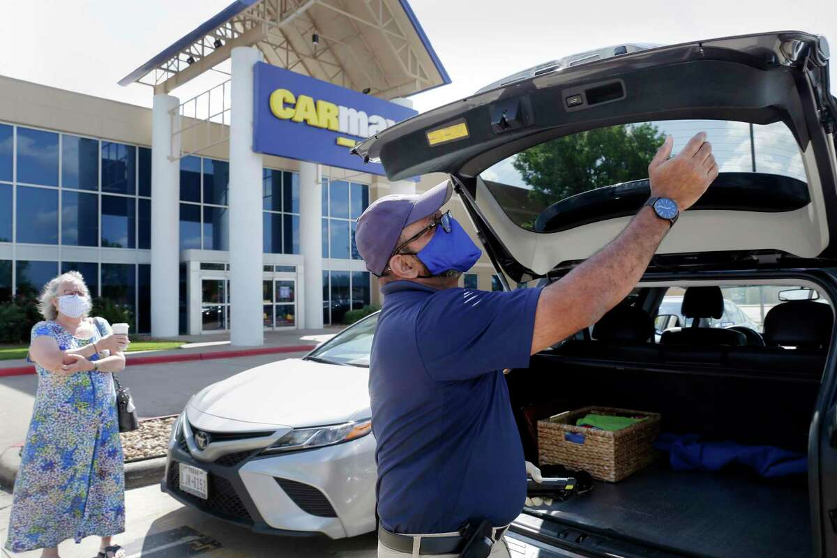 """CarMax buyer Bobby Sheik, right, looks over a Lexus SUV brought in by the owner, left, for a possible sale Monday, June 8, 2020 in Houston, TX. Sheik goes over the vehicle in the parking lot, noting everything into a handheld computer before any test drive. Then, an initial offer is made to the owner. CarMax has instituted a """"limited touch"""" system that reduces contact with both the owners and vehicles as a result of the COVID-19 pandemic."""