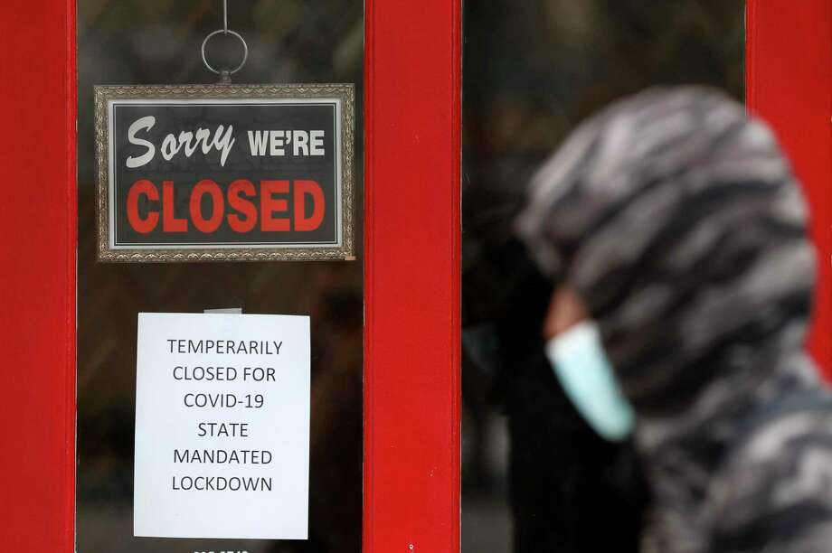 In May, a pedestrian in Michigan stops at a a closed gallery. The recent positive jobs report will encourage Republicans to push for more openings and less aid — a disastrous combination. Photo: Paul Sancya / Associated Press / Copyright 2020 The Associated Press. All rights reserved