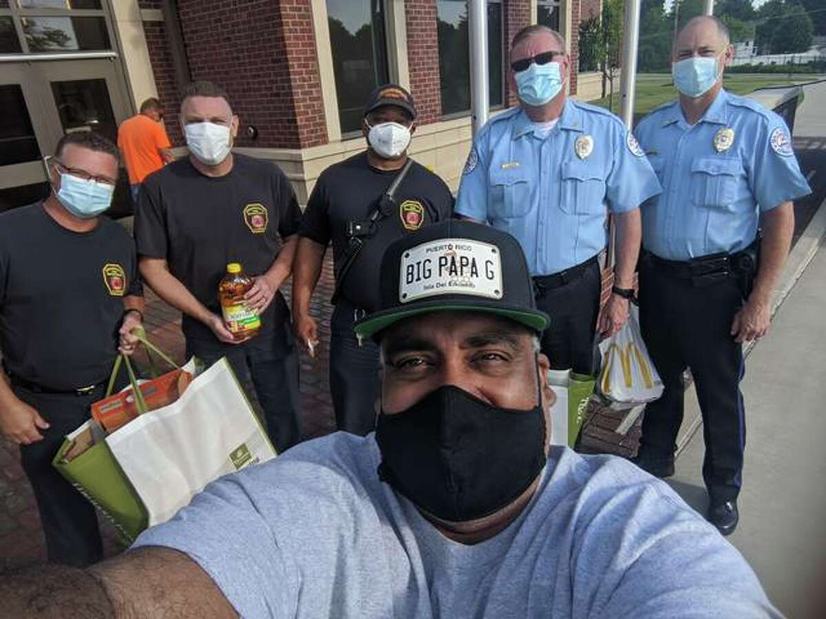 Greg Horta takes a selfie with local first responders in front of the Edwardsville Public Safety Building.
