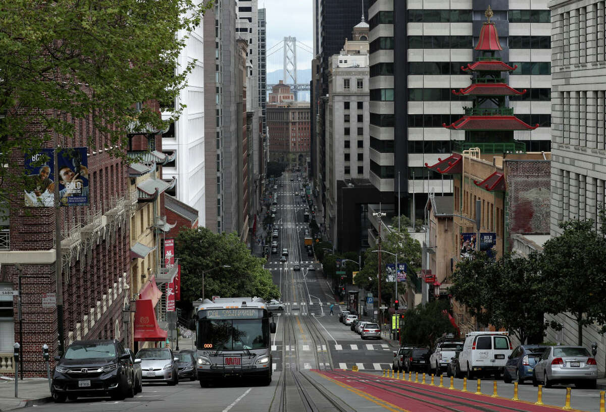 FILE.- A San Francisco MUNI bus travels along an empty California Street during the coronavirus (COVID-19) pandemic on April 6, 2020. Shortly after the SFMTA announced they would no longer transport police officers to protests, the SFPOA lashed back on social media.