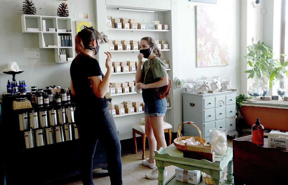 Stephanie Hernandez talks with shopper Katherine Leister at Down To Earth in Beaumont Thursday. The The herbal, organic boutique waited until this week to reopen and requires customers, limited to two in the store at one time, to wear masks and sanitize their hands upon entry.  Photo taken Thursday, June 4, 2020 Kim Brent/The Enterprise Photo: Kim Brent / The Enterprise / BEN