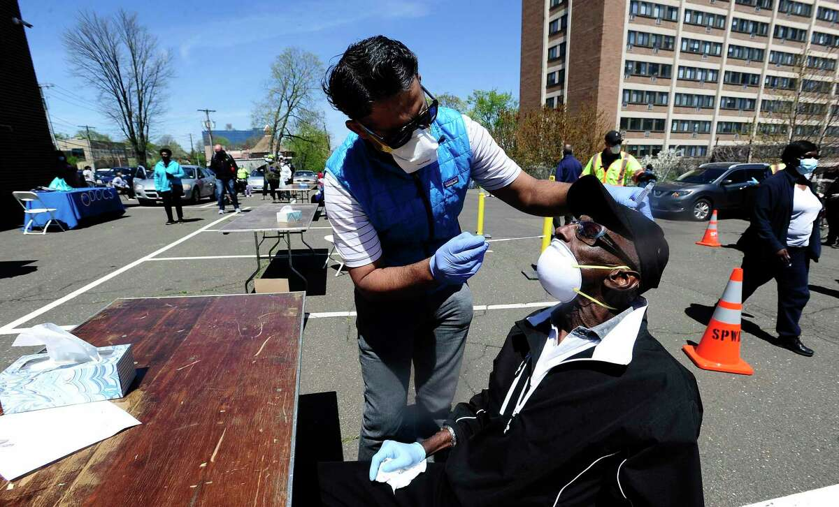 Dr. J.D. Sidana of DOCS Urgent Care Stamford administers a COVID-19 nasal swab test on Robert Hayes, 73, of Stamford at a walk-up testing site for the coronavirus at AME Bethel Church in Stamford May 2.