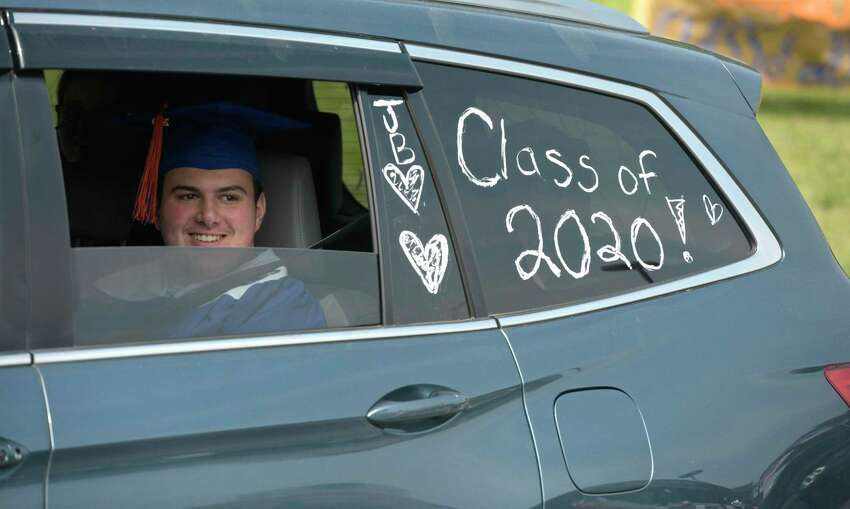 Jackson Scott Benz waits in a SUV to take part in the 2020 Danbury High School graduation, Wednesday, June 10, 2020, at Danbury High School, Danbury, Conn. Graduation is taking place over three days, June 10, 11, and 12.