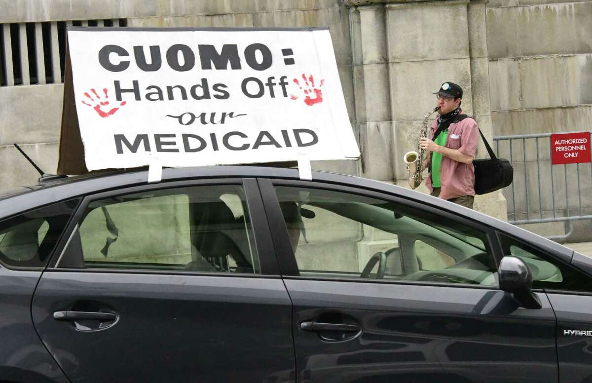 """Dan Plaat, secretary of local Green Party, plays the saxophone while a parade of cars circle the New York State Capitol honking their horns with signs such as """"Cuomo: Hands Off our Medicaid"""" on Wednesday, June 10, 2020 in Albany, N.Y. (Lori Van Buren/Times Union)"""