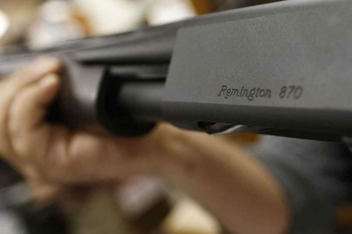 In this March 1, 2018 file photo, the Remington name is seen etched on a model 870 shotgun at Duke's Sport Shop in New Castle, Pa. For years, the gun industry has been immune from most lawsuits, but a recent ruling allowing families of victims in the Newton school shooting to challenge the way an AR-15 used by the shooter was marketed.