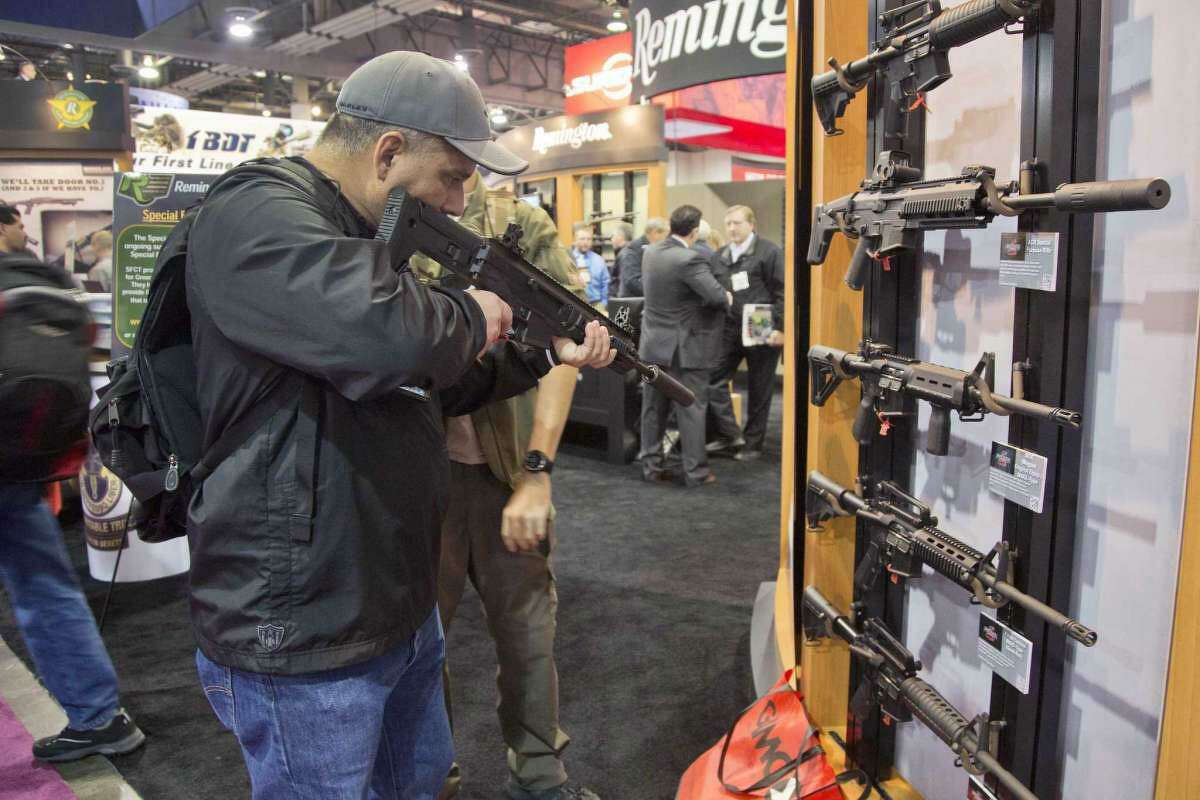 Stuart Konicar of Scottsdale, Ariz., looks down the sight of a Remington Adaptive Combat Rifle on display at the Remington Defense exhibit during the 35th annual SHOT Show, Tuesday, Jan. 15, 2013, in Las Vegas.