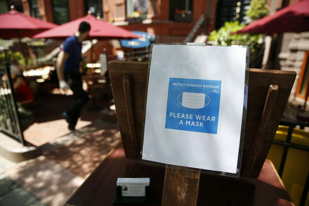 FILE-- As San Francisco restaurants begin to offer outdoor dining, health safety steps will need to be implemented amid the coronavirus pandemic. (A sign at the outdoor host stand asks diners to wear a mask at La Voile on Newbury Street in Boston on June 8, 2020.)