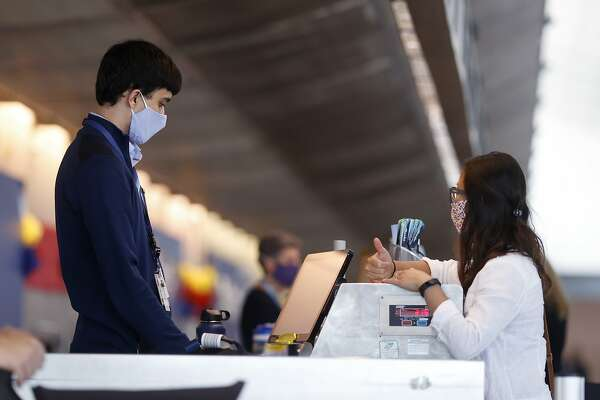 An Alaska Airlines ticketing agent, left, checks in a passenger at the counter in Denver International Airport as travellers deal with the effects of the new coronavirus, Wednesday, June 10, 2020, in Denver. (AP Photo/David Zalubowski)