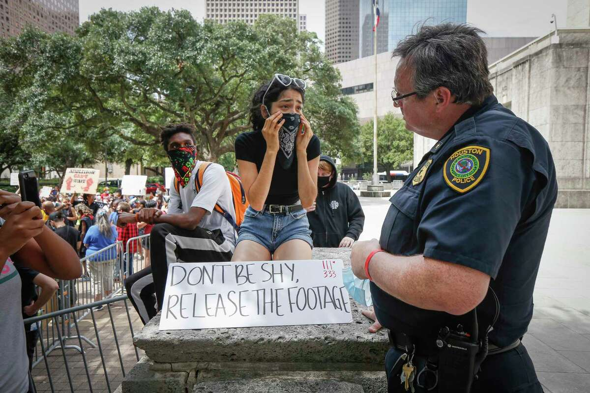 Aaliyah Pozo talks to Houston Police Commander Wyatt Martin during a rally to eliminate police misconduct Wednesday, June 10, 2020, in Houston.