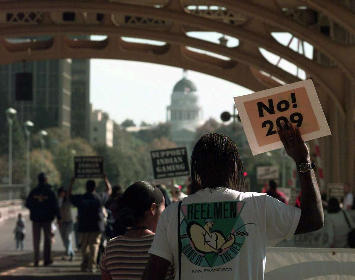 Michael Jefferson of Vallejo, Calif., carries his anti-affirmative Prop. 209 sign across the Tower Bridge with the State Capitol in the background Monday, Oct. 27, 1997, in Sacramento, Calif. Jefferson marched with hundreds of others in Jesse Jackson's Save the Dream march in Sacramento. (AP Photo/Eric Risberg). ALSO RAN: 5/18/98,