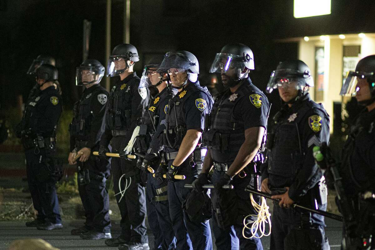 Area police officers form a line between protesters and the Vallejo Police Department during a protest against the police killing of Sean Monterrosa in Vallejo, Calif., Friday, June 5, 2020
