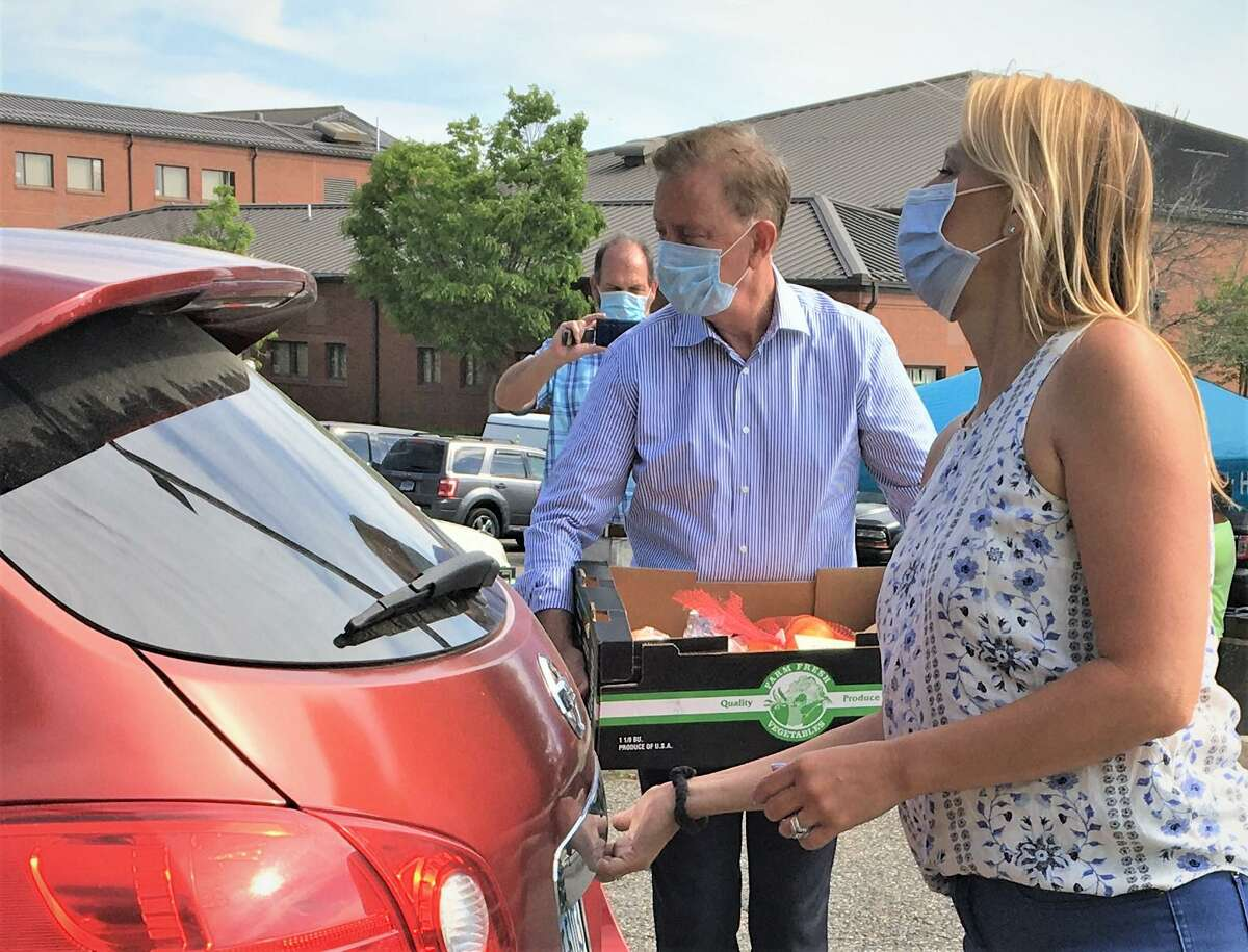 Gov. Ned Lamont and Rep. Michelle Cook, D-Torrington, helped give away boxes of produce Wednesday through the Friendly Hands Food Bank at Torrington Middle School. The event was scheduled for 8 a.m. until noon. The food ran out at 10.