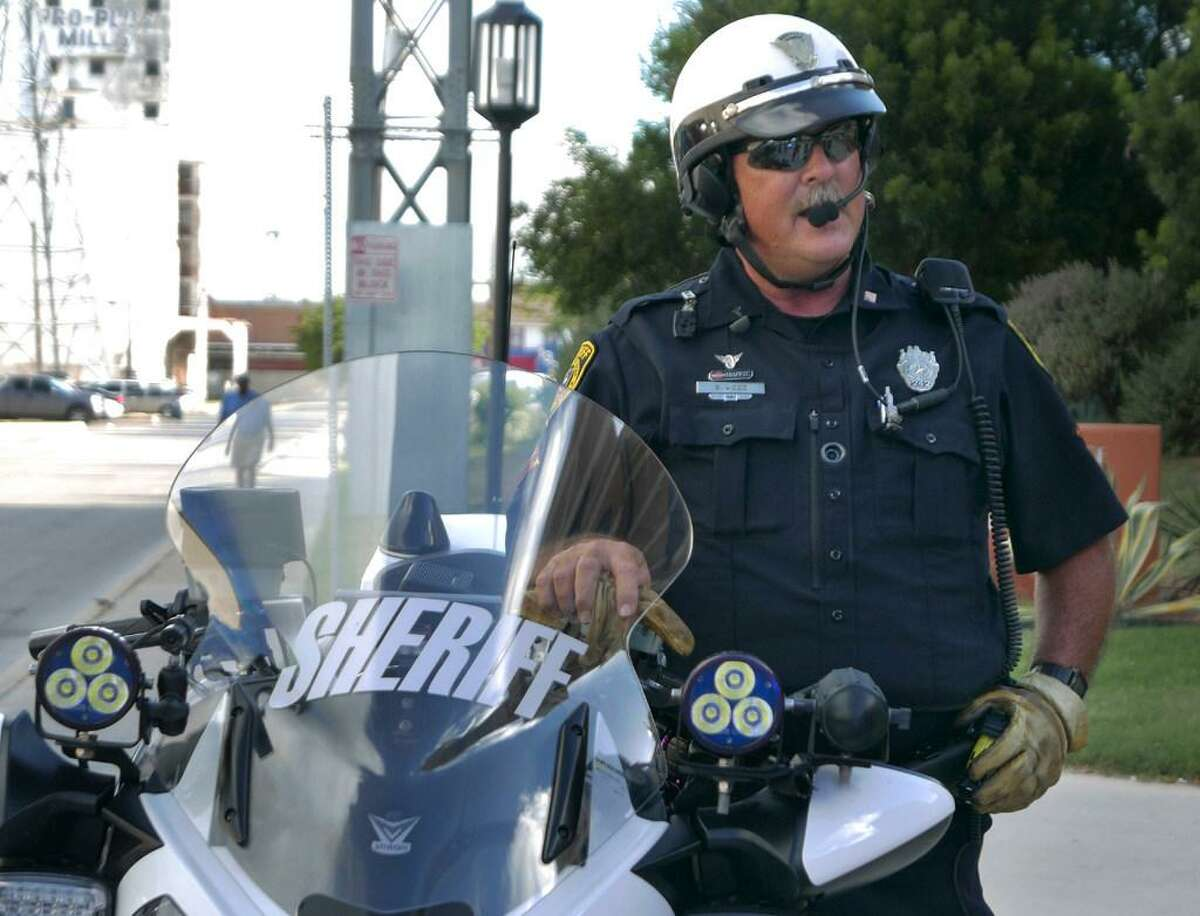 Patrolman Steve Wood of the Bexar County Sheriffs Office wears a BodyWorn camera, visible as the small circle in the center of his uniform shirt, as he stands by his motorcycle, which is also equipped with two cameras. The forward-facing camera on the cycle can be seen at lower left, by the object with three lamps. Friday, Aug. 5, 2016.