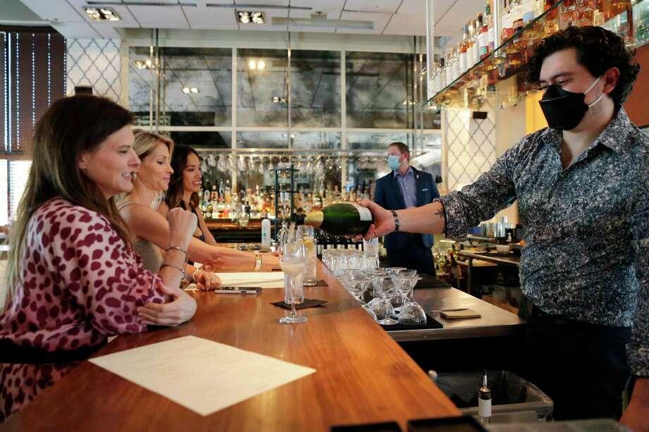Customers sit at the bar as bartender Mauro Cisneros pours drinks at Doris Metropolitan steakhouse. Servers wear masksto prevent the spread of coronavirus. Photo: Michael Wyke / Contributor / © 2020 Houston Chronicle