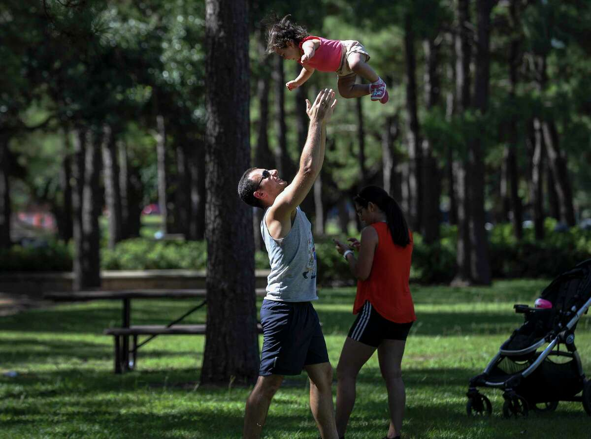 John Saydi tosses his 14-month-old daughter Selah into the air Wednesday, June 10, 2020, at Hermann Park in Houston. Saydi, his daughter and his wife Daniella said they visit the park frequently but don't go out otherwise. John Saydi said he works in healthcare, and he said he monitors infection numbers as the pandemic stretches into the summer.