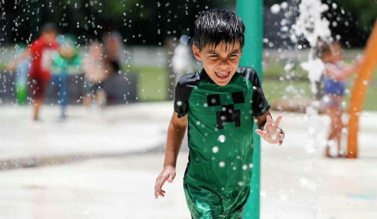 Grayson Loveless yells as he runs through water during a visit to the splash park at Martin Luther King, Jr. Park, Wednesday, June 10, 2020, in Conroe.