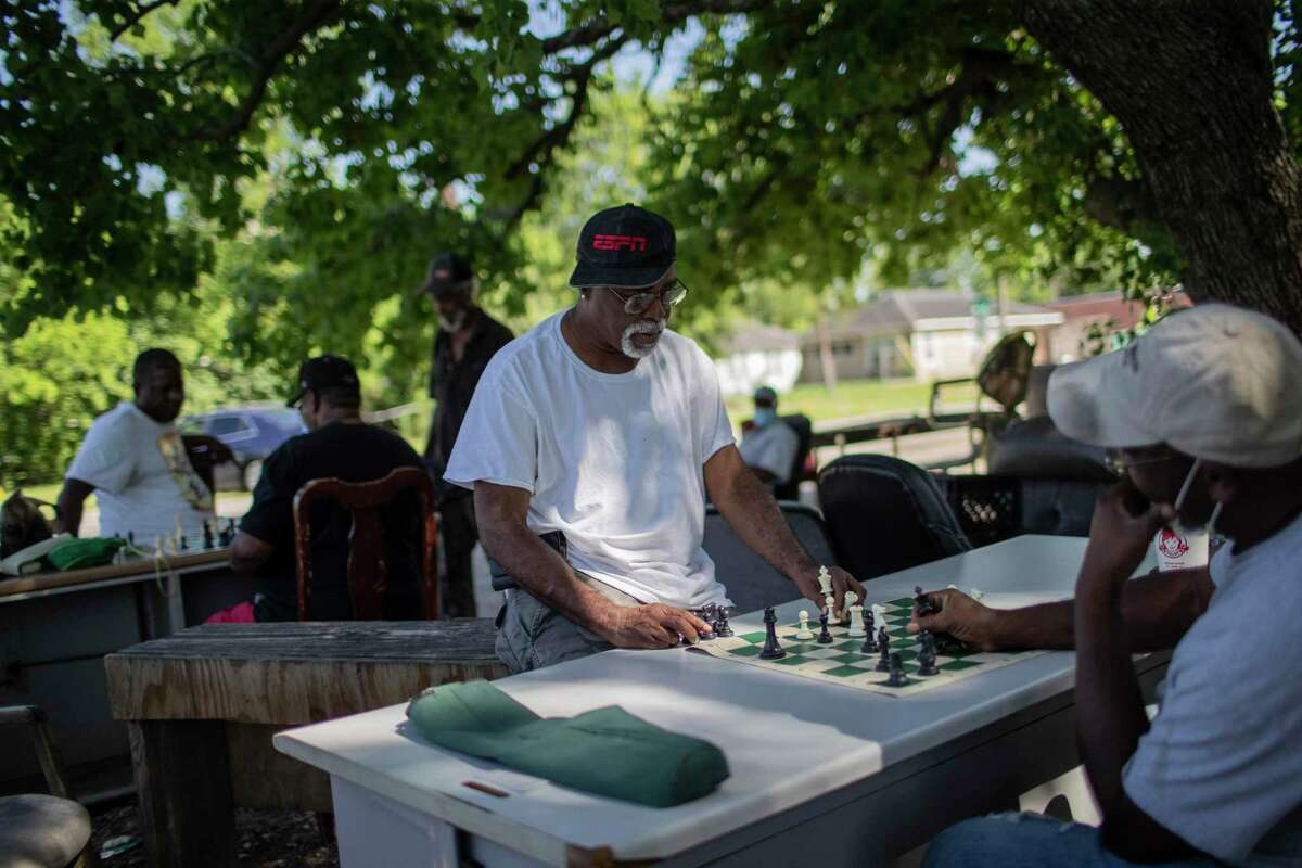 Yank Brown plays chess with a friend under a tree in Third Ward on Wednesday, June 10, 2020, in Houston. Brown won that game.