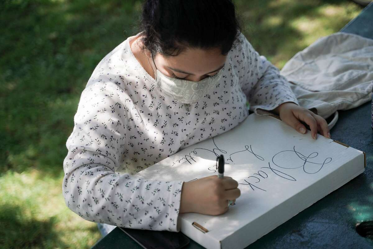 Emily Iba�ez Arroyo, 18, of Windsor, designs a signed before a protest to Defund the Petaluma Police Department at Walnut Park in Petaluma, Calif., on Wednesday, June 10, 2020.