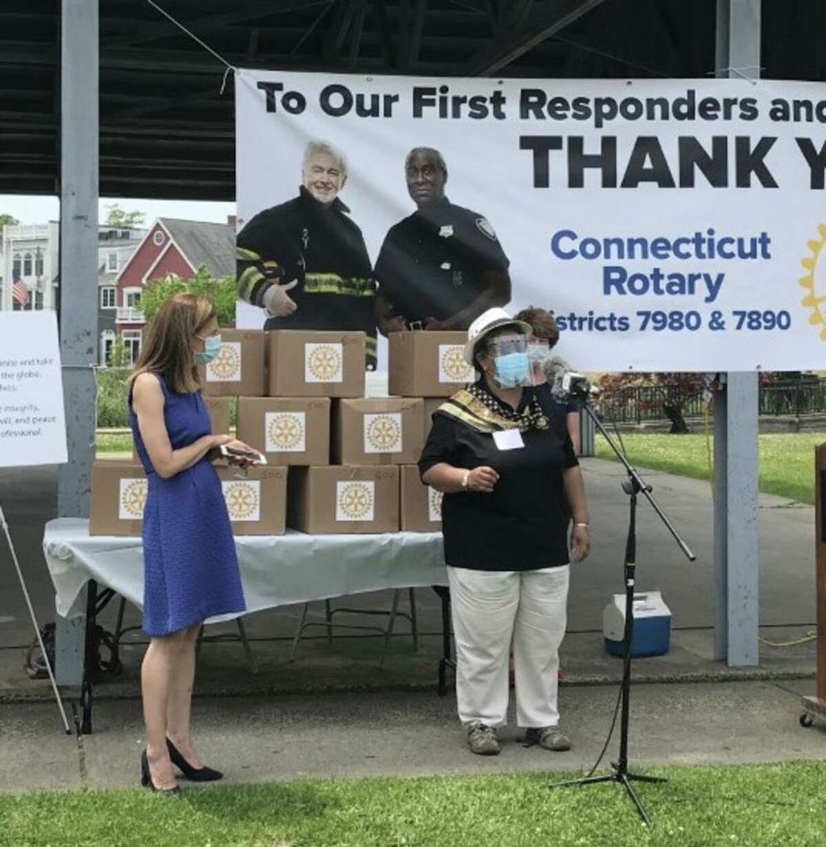 Stephanie Philips, current assistant governor of Stratford Rotary, shows off one of the 6,000 masks to Lt. Gov. Susan Bysiewicz that Rotary dollars helped create.